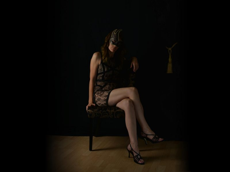 Dark image of a call girl seated in a room