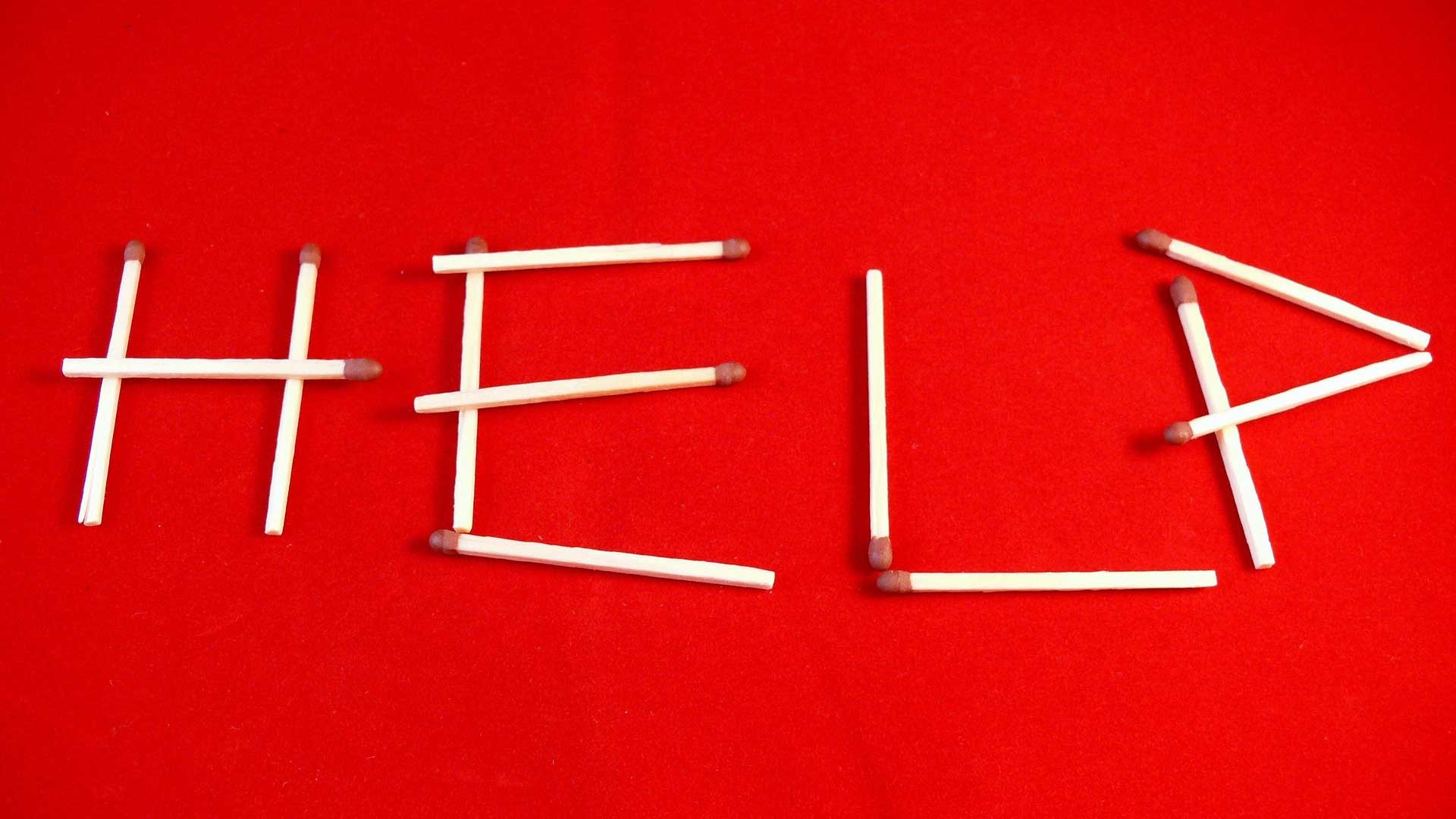 Word help written with matchsticks on a red background